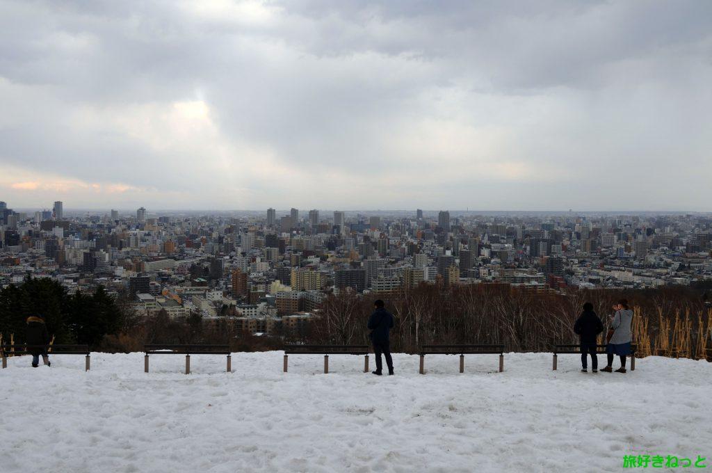 旭山記念公園の雪解けが始まり札幌の景色を見に人が訪れていました